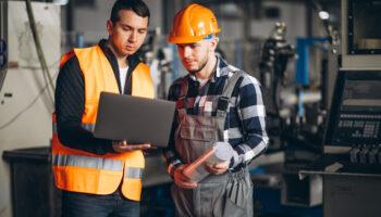 gerente de produção industrial analisando indicadores de manutenção no notebook com outro colaborador